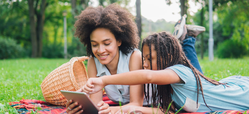 A girl and her mom reading outdoors